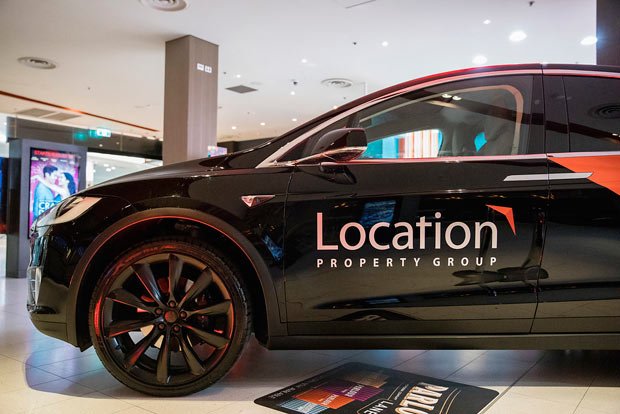 Tesla with Location Property Group Logo